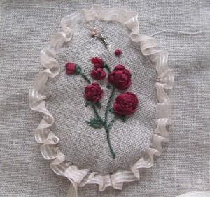 """Un """"médaillon"""" froufrouté, orné de roses brodées au ruban, en médaillon"""