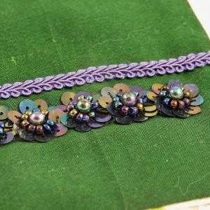 Des fleurs en cuvettes et perles, ainsi qu'un galon épi décore de devant